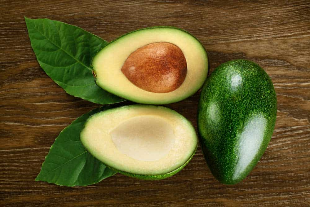 Avocado tree produces oval or egg-shaped fruit that has fleshy structure and large seed in the middle.